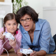 Grandmother playing a video game with her granddaughter — Stock Photo