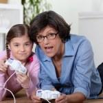 Großmutter ein Video-Spiel mit ihrer Enkelin — Stockfoto