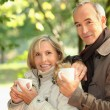 Middle-aged couple drinking coffee in park — Stock Photo