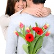 Man with surprise flowers for his girlfriend — Stock Photo