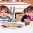 Two grumpy toddlers waiting for their pancakes - Stock Photo