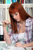 A young red-hair studying for exams. — Stock Photo