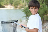 Little boy at a riverside with a landing net — Stock Photo