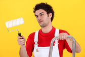 Man on step-ladder holding paint roller — Stock Photo
