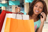 Woman with her shopping bags and talking on her phone — Stock Photo