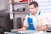 Man checking plumbing products on a computer database — Stock Photo
