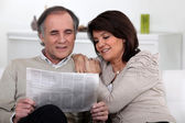 Couple reading the newspaper together — Stock Photo