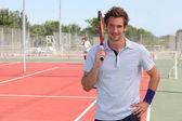 Adam omuz üzerinden raket tutarak açık tenis kortu üzerinde durdu — Stok fotoğraf