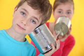 Two kids talking through linked cans. — Stock Photo