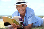 Elderly man reading a book outside — Stock Photo