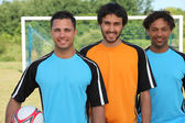 Three football players standing in front of goal — Stock Photo
