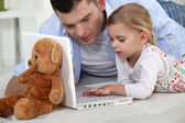 Young girl playing with her father's laptop — Stock Photo