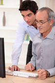 Elderly man learning computer skills — Stock Photo