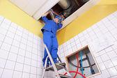 Plombier travaillant sur une échelle — Photo