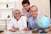 Young man and senior couple seeking a route on a map — Stock Photo