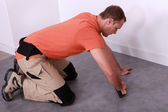 Portrait of a man laying linoleum — Stock Photo