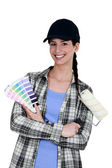 Female painter holding a roller brush and a color chart — Stock Photo