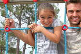 Young girl on a climbing frame with her dad — Stock Photo