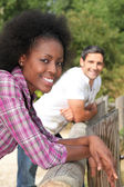 A black woman and a man leaning against wooden barrier — Stock Photo