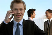 Young businessman on the phone in front of colleagues — Stock Photo