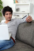 Man using his credit card online — Stock Photo