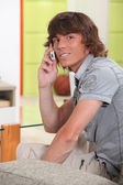 Young man using his cellphone indoors — Stock Photo