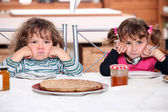Two grumpy toddlers waiting for their pancakes — Stock Photo