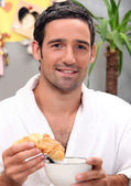 Man dipping croissant in coffee — Stock Photo