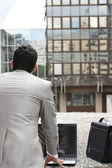 Back view of a businessman standing outside with computer and briefcase — Stock Photo