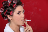 Woman smoking with her hair in rollers — Stock Photo