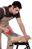 Man cutting a piece of wood — Stock Photo