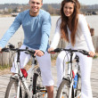 Young couple riding bikes along a river - Stok fotoğraf
