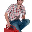 Builder kneeling by tool box — Stock Photo #8029617