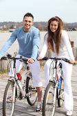 Young couple riding bikes along a river — Stock Photo