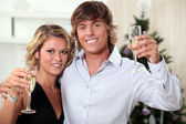 Young couple celebrating Christmas with champagne — Stock Photo
