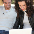 Couple using a laptop outdoors — Stock Photo