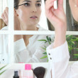 Stock Photo: Woman applying make-up