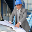 Architect looking at plans on a car bonnet — Stock Photo