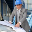 Stock Photo: Architect looking at plans on car bonnet