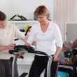 Blonde middle-aged woman on treadmill coached by physiotherapist — Stock Photo