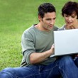 Man and woman on the grass with laptop — Stock Photo #8031995