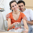 Couple unpacking glassware — Stock Photo #8032367