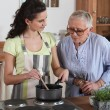Young woman cooking for an elderly lady — Stock Photo #8032491