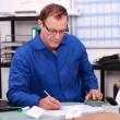 Stock Photo: Builder working on paperwork in an office