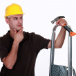 Doubtful man holding a hammer and a ladder — Stock Photo #8034273