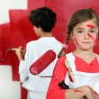 Children painting a wall red — Stock Photo #8034453