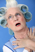 Senior woman with curlers in her hair looking very surprised — Stock Photo