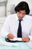 Businessman noting appointment on organizer — Stock Photo
