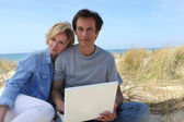 Couple on the dunes using laptop computer — Stock Photo