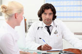 Doctor and female patient at surgery — Stock Photo